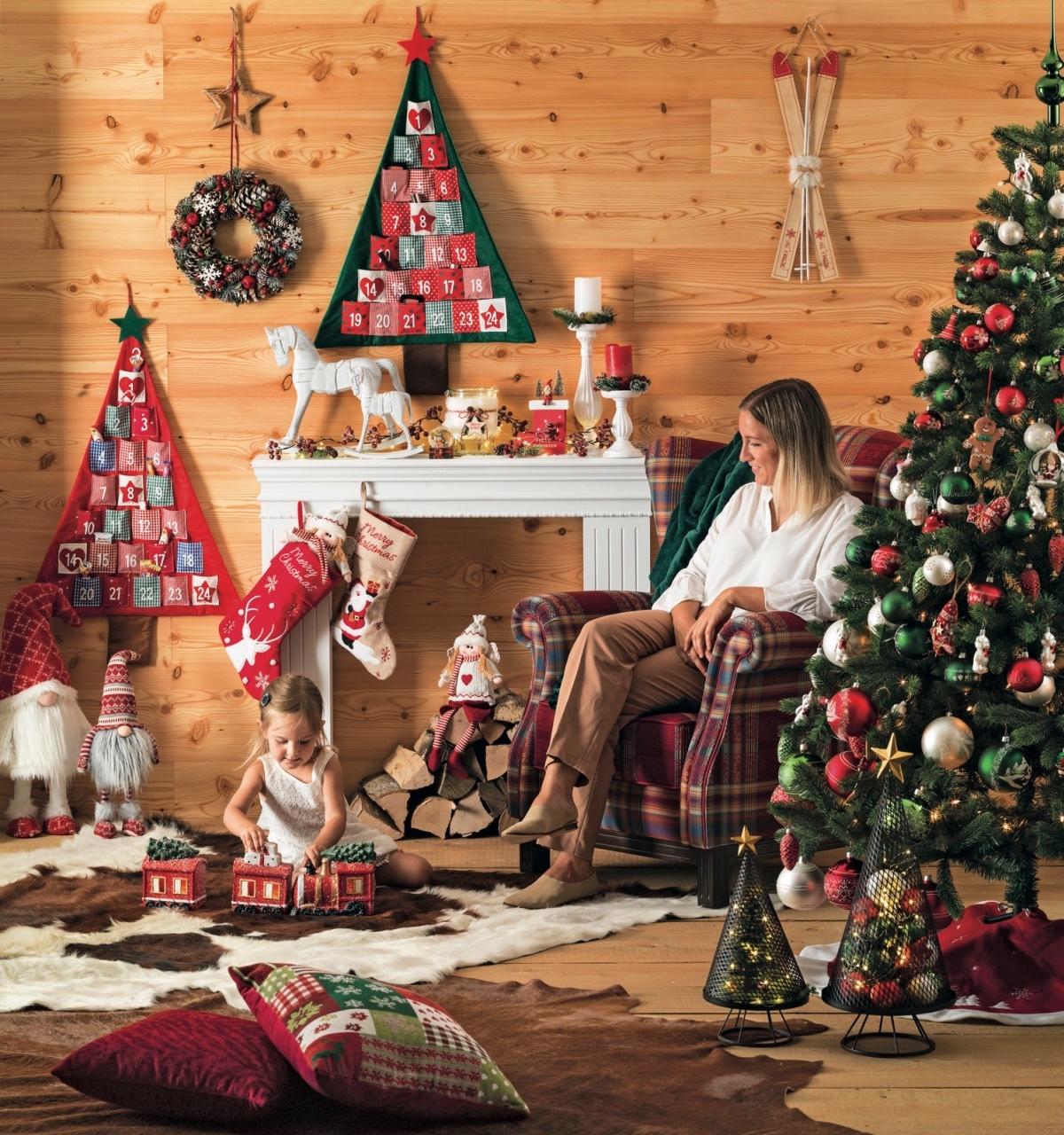 Frau und Kind sitzen vor Kamin und Christbaum in weihnachtlich geschmücktem Raum