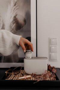 frau hält duftkapsel in raumdiffuser aromea aera