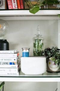 aromea aera duftmarketing diffuser in regal mit blumen und büchern