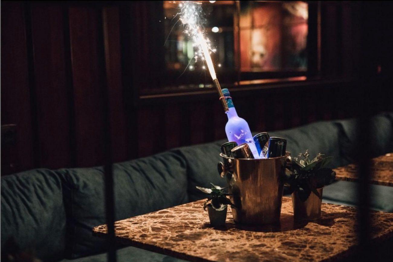 Flasche in Bar mit Sternspritzer auf Tisch