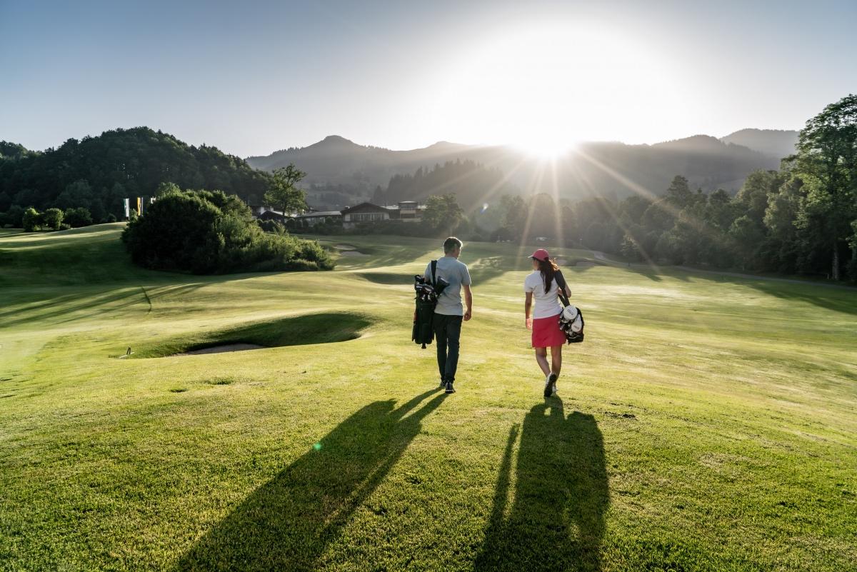 Mann und Frau am Golfplatz im Grünen mit Berge und Sonne