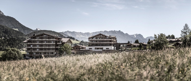Hotel im Sommer mit Wiese und Bergen