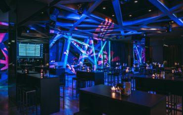 Veranstaltungssaal mit blauem Licht und futuristischer Deko und Tischen