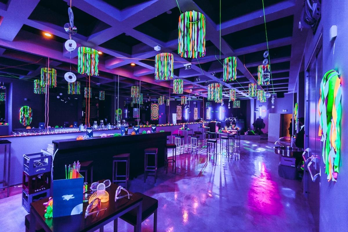 Veranstaltungssaal mit blauem Licht und futuristischer Deko, Tischen und Bar
