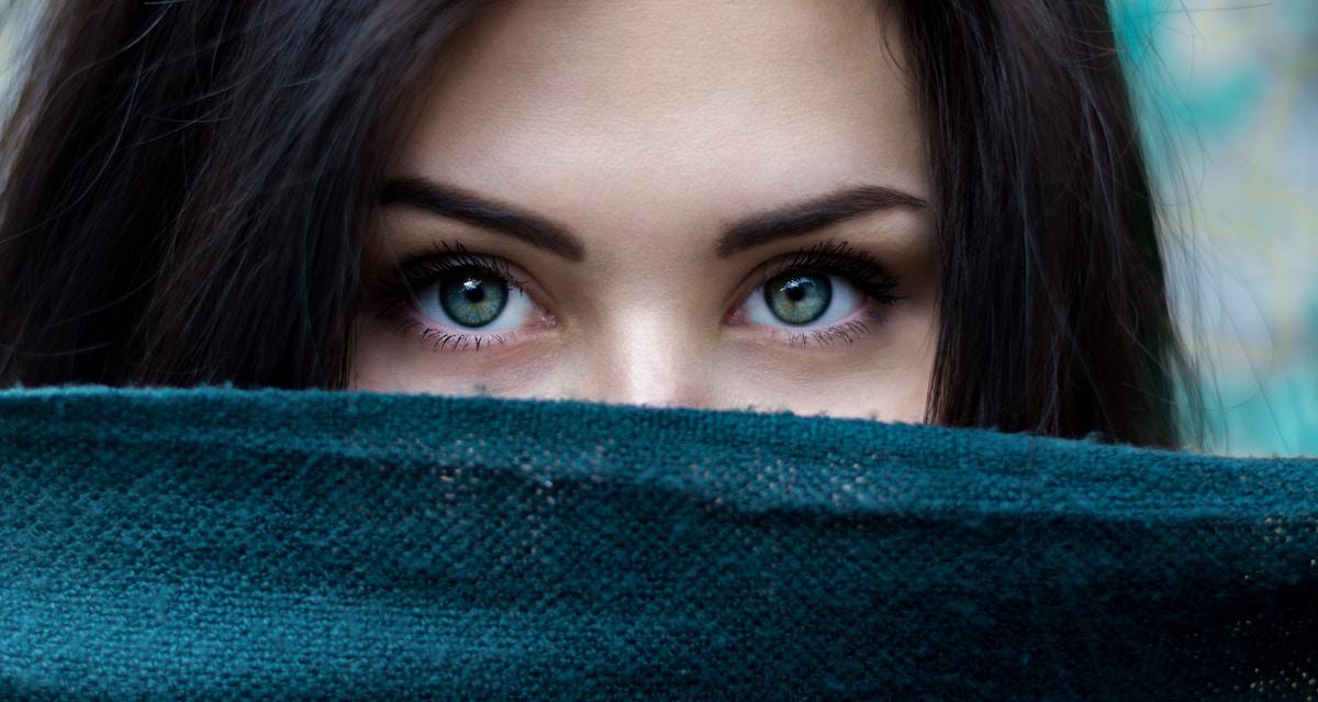 Eine Frau versteckt sich hinter einem Schal