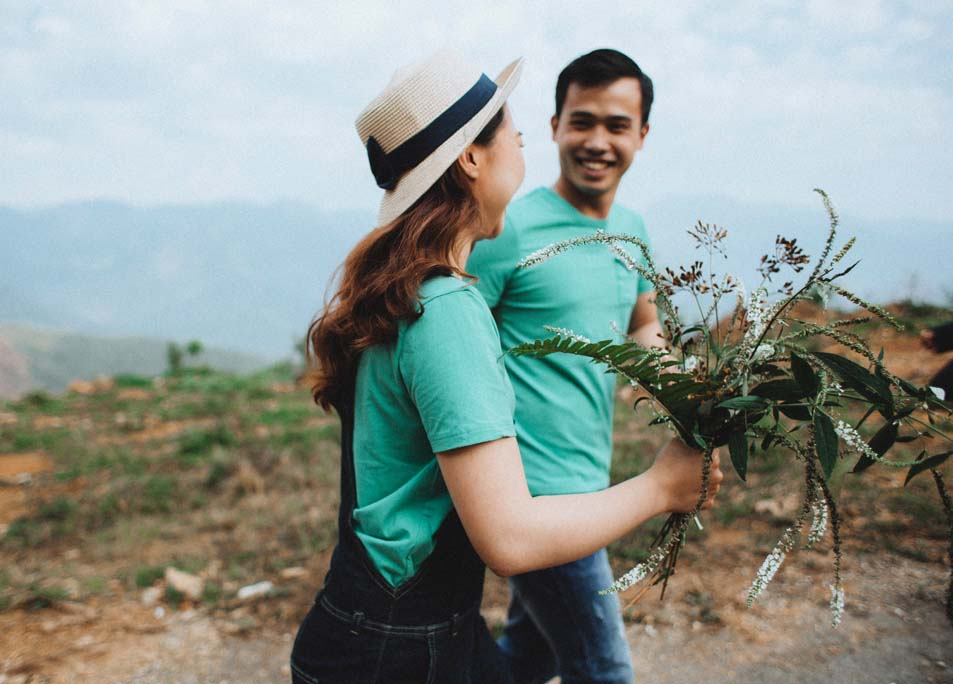 Mann und Frau gehen nebeneinander mit Blumen in der Hand und Hut