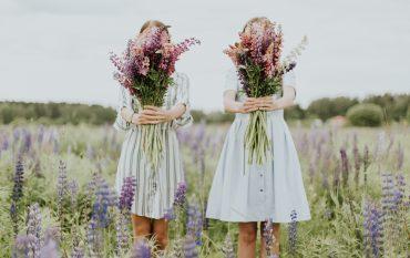 Zwei Mädchen stehen in einer Weise mit Lavendel und halten einen Strauß Blumen in der Hand