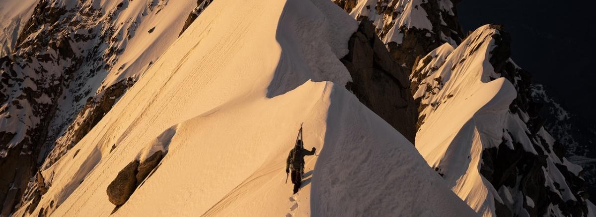 Mann geht am Bergkamm entlang, Schnee, Winter