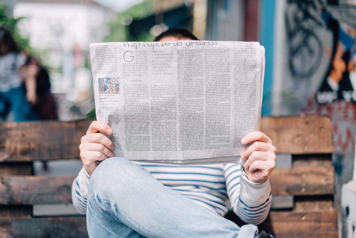 Mann sitzt auf Parkbank und liest Zeitung