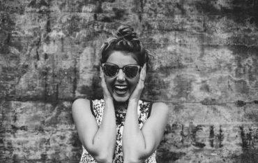 Frau lacht mit Sonnenbrille, schwarz weiß